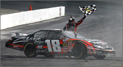 Kyle Busch waves the checkered flag from his Toyota after winning the NASCAR Nationwide Series Camping World RV Sales 200 in Loudon, N.H.