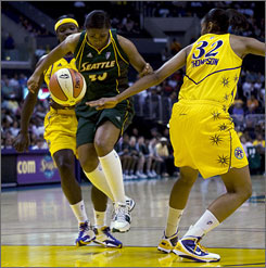 Storm guard Tanisha Wright, center, loses the ball against the Sparks' Tina Thompson, right, and Marie Ferdinand-Harris during the first quarter. Ferdinand-Harris scored a season-high 15 points in the Sparks' 82-55 win.
