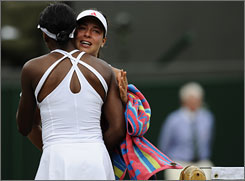Venus Williams hugs Ana Ivanovic after she retired in the second set of their fourth-round match at Wimbledon on Monday. A thigh injury forced Ivanovic to call it quits, sending Williams into the quarterfinals at the All England Club.