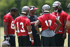 New Bucs coach Raheem Morris, center, inherited a team that went 9-7 last year and lost its final four games.