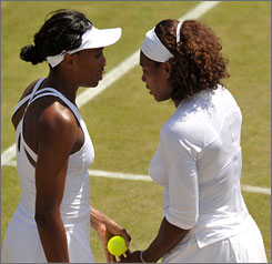 Venus, left, and Serena Williams play together on court during a doubles match at Wimbledon. In singles play, however, the duo could be on the same court together, facing off for the championship Saturday on Centre Court.