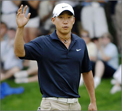 Anthony Kim acknowledges the gallery after a birdie putt at the eighth green as part of his round of 62.