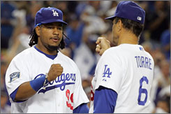 Manny Ramirez, sporting hair a bit shorter than this year, has a fist bump for Dodgers manager Joe Torre during the 2008 playoffs.
