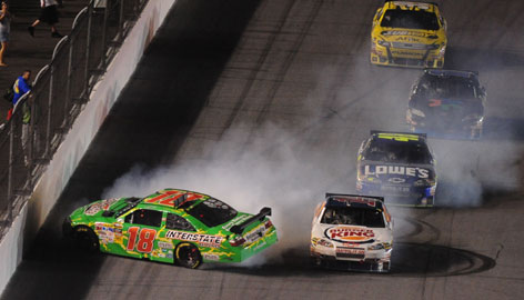 Kyle Busch (18) spins after contact with Tony Stewart, front right, on the last lap of the Coke Zero 400 at Daytona International Speedway.