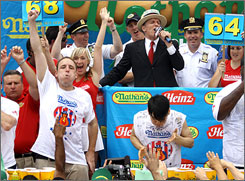 Joey Chestnut celebrates after clinching his third consecutive hot dog title by eating 68 weiners in 12 minutes.