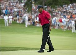 Tiger Woods pumps his fist as he sinks a birdie putt on the sixth hole during the final round of the AT&T National at the Congressional Country Club on Sunday. Woods held off  Hunter Mahan, finishing at 13 under to win his own tournament.