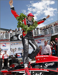 Justin Wilson leaps out of his car after capturing the winner's laurels at Watkins Glen International.