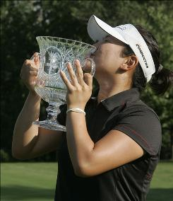 Eunjung Yi kisses the trophy after winning the Jamie Farr Owens Corning Classic golf tournament Sunday. Yi and Morgan Pressel tied at 18-under par and had to play one playoff hole for the title.