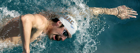 Michael Phelps warms up at a meet in June using his traditional freestyle stroke. He'll test a straight-arm stroke at nationals this week.