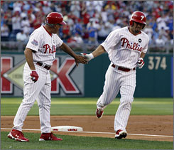 The Phillies' Shane Victorino, right, celebrates with third base coach Sam Perlozzo after he hit a two-run homer in the first. Victorino went 4-for-5 with four RBI.