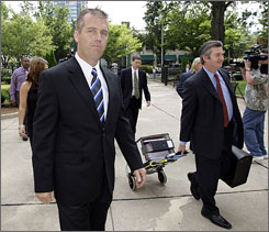 NASCAR driver Jeremy Mayfield, left, arrives at the federal courthouse in Charlotte on July 1. Mayfield won a temporary injunction to stay his suspension.