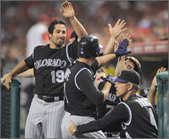 The playoff-hopeful Colorado Rockies have had many celebrations involving high-fives since Jim Tracy, lower right, replaced Clint Hurdle as manager on May 29.