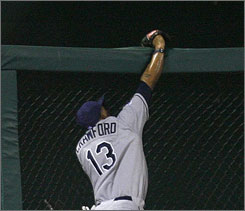 Rays outfielder Carl Crawford, the All-Star Game MVP, robs the Rockies'      Brad Hawpe of a potential go-ahead home run in the seventh inning.