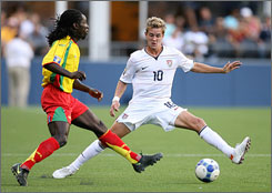 Stuart Holden, right, dribbling the ball against Grenada's Jason James during a Gold Cup match on July 4, helped the USA earn first place in Group B with a game-tying goal against Haiti last weekend.