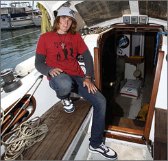 Zac Sunderland poses aboard his 36-foot Intrepid boat at the Del Rey Yacht Club in Marina del Rey, Calif. The 17-year-old left Marina del Rey on June 14 of last year and returned Thursday after sailing around the world alone, becoming the youngest person to achieve the feat.
