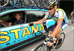 Lance Armstrong, shown talking with Astana team manager Johan Bruyneel during Stage 10, has lashed back at a French sports minister who said the team was 'avoiding' a doping test earlier this week.