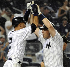 The Yankees' Mark Teixeira, right, celebrates with Derek Jeter after Teixeira hit a three-run home run during the seventh inning.