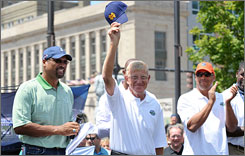 Lou Holtz, Notre Dame football coach from 1986-1996, tips his cap during the Hall of Famer Pep Rally. At left is Mark May and right another of this year's enshrinees, Don McPherson.