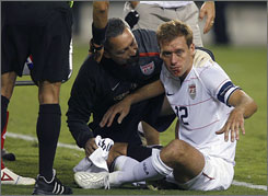 The USA's Jimmy Conrad receives medical attention after getting hit in the head Saturday, forcing him out of the game.