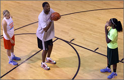 Georgia Ice coach and former NBA player Antonio Davis, center, gives shooting tips to Kylee Smith, left, and Diamond DeShields. Davis coached the Ice to an AAU 13-and-under national title.