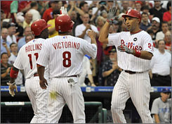 Phillies left fielder Raul Ibanez, right, celebrates at home plate with teammates Jimmy Rollins and Shane Victorino after hitting a three-run homer during the first inning.