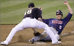 Minnesota's Michael Cuddyer is tagged out by Oakland pitcher Michael Wuertz  or is he? The Twins argued the Cuddyer beat the throw that followed a wild pitch. But umpire Mike Muchlinski saw it in Oakland's favor, ending a 14-13 victory for the A's.