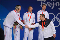 The USA's Michael Phelps, right, shakes hands with France's silver medal-winning 4x100 relay in August in Beijing. The two teams meet again this weekend in the world championships.