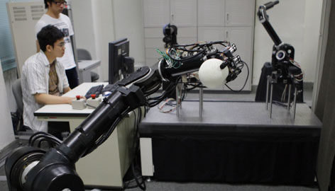 A pitching robot grips a ball during a demonstration of its capabilities against a batting robot, right, at the University of Tokyo.