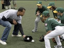 New York Yankees third baseman Alex Rodriguez shows members of the Athletics Little Leaguers team how to field grounders during a baseball clinic, part of the Yankees' HOPE (Helping Others Persevere and Excel) Week in New York.
