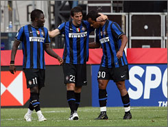 Diego Milito, center, is congratulated by Inter Milan teammates Alessandro Amantino (30) and Sulley Muntari after scoring one of his two goals in the second half of his team's victory over Serie A foe AC Milan at Gillette Stadium.