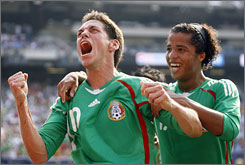 Mexico's Guillermo Franco, left, celebrates with teammate Giovani dos Santos after Franco scored his team's fifth goal in their 5-0 thumping of the United States in the Gold Cup final.