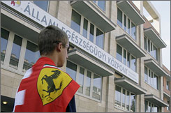 A Ferrari fan stands vigil for F1 driver Felipe Massa outside a Budapest hospital Monday.