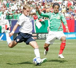 Stuart Holden kicks the ball as Mexico forward Giovani Dos Santos closes in during the Gold Cup final.
