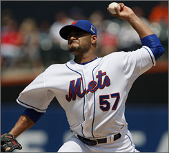 Mets ace Johan Santana fires toward the plate during the first inning against the Rockies.