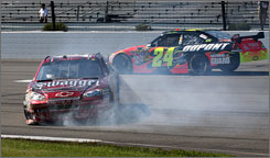 Tony Stewart's car slides to a stop at the exit of Pocono's third turn as Jeff Gordon takes evasive action to the high side.