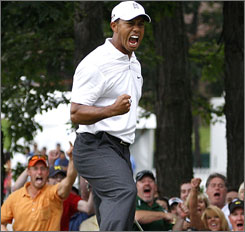 Tiger Woods cheers as his birdie putt drops on the 17th hole during his third-round 65.