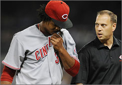 Reds starter Edinson Volquez listens to a member of the team's training staff as he leaves Cincinnati's game against San Diego on May 16.