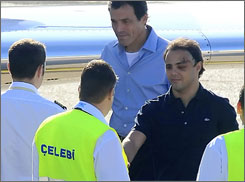 Felipe Massa shakes hands with officials at the Ferihegy Airport in Budapest before boarding his flight home to Brazil.