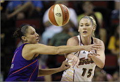 The Seattle Storm's Lauren Jackson, right, makes a pass as the Phoenix Mercury's Diana Taurasi defends during the first quarter. Taurasi scored 19 points to lead the Mercury to a 101-90 overtime win.