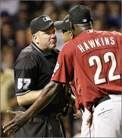 Astros' manager Cecil Cooper, center, defends his relief pitcher LaTroy Hawkins with home plate umpire Mike Everitt after Everitt ejected Hawkins in the eighth inning.