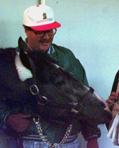 Ernest Paragallo stands with Kentucky Derby hopeful Unbridled's Song at Churchill Downs in 1996.