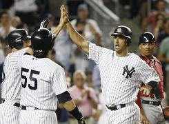 The Yankees' Jorge Posada, right, is greeted by his teammates after slugging a three-run homer in the fourth inning Thursday night.
