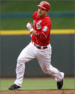 Reds first baseman Joey Votto legs out a triple in a July game vs. the Cardinals. Votto has thrived at the plate, overcoming health issues and the death of his father.