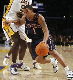 Marcus Williams, then a New Jersey Net, drives past the Lakers' Kwame Brown.