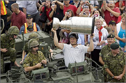 Sidney Crosby hoists the Stanley Cup as he rides atop a light armored vehicle in Cole Harbour, Nova Scotia.