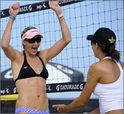 Kerri Walsh, left, celebrates with new partner Rachel Wacholder after winning their opening-round match at the AVP Hermosa Beach Open. The duo would win two more matches before losing one and being relegated to the contenders' bracket.