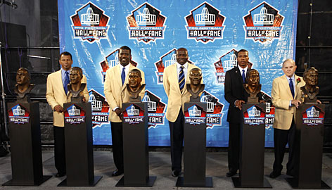 From left, Rod Woodson, Randall McDaniel, Bruce Smith, Bob Hayes Jr. (representing his deceased father Bob Hayes), and Ralph Wilson pose at the Pro Football Hall of Fame induction ceremony. On the far left is the bust of the late Derrick Thomas, the sixth member of the Class of 2009.