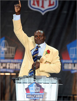 Bruce Smith salutes the Canton, Ohio crowd after his induction speech. Smith, a two-time defensive player of the year, is the NFL's all-time sacks leader.