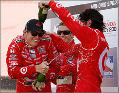Scott Dixon, left, gets a champagne dousing from teammate and Mid-Ohio runner-up Dario Franchitti as third-place Ryan Briscoe watches the festivities in Victory Lane.