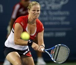 Kim Clijsters returns a volley to Marion Bartoli of France during their first-round match at the Cincinnati Open.